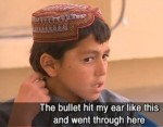 Screen-captured image of 11-year-old Sediqullah of Alkozai pointing to the bullet hole he received in the ear on March 11, 2012, in an interview with DatelineSBS in late March, 2012